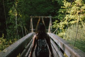 woman-backpacking-across-bridge